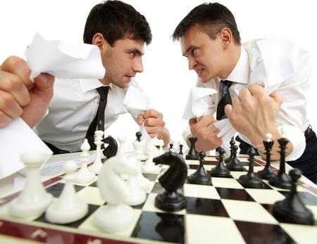 aggressively: Due uomini con carte che cercano a vicenda in modo aggressivo, mentre giocano a scacchi