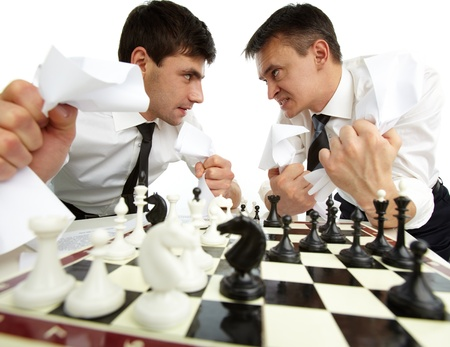 aggressively: Two men with papers looking at each other aggressively while playing chess