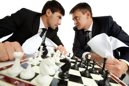 aggressively: Due uomini con le carte guardarsi aggressivo durante il gioco degli scacchi