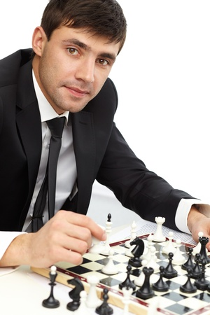 Image of successful businessman looking at camera while playing chess photo