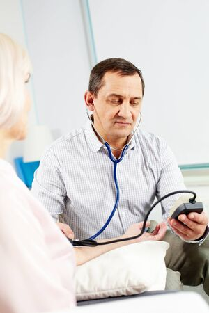 Portrait of mature man measuring blood pressure of his wife Stock Photo - 11622360