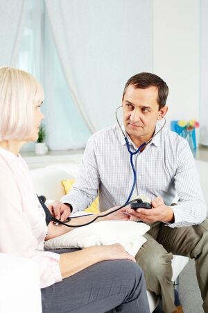 Portrait of mature man measuring blood pressure of his wife at home photo