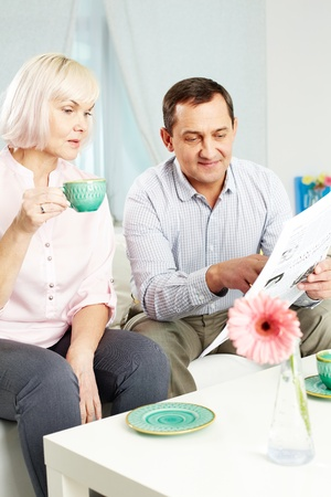 Portrait of mature man and his wife reading newspaper in the morning at home photo