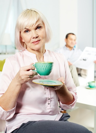 Portrait of mature woman with cup looking at camera on background of her husband Stock Photo - 11622373