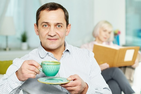 Portrait of happy senior man with cup and his wife reading book behind photo