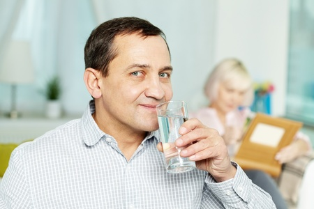 man drinking water: Portrait of happy senior man drinking water from glass and his wife reading book behind