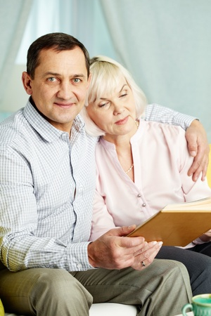 Portrait of mature man embracing his wife while they looking through their photographs photo