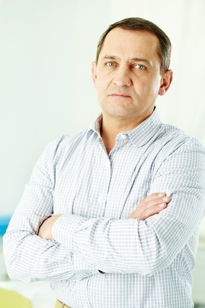 Portrait of mature man with crossed arms looking at camera photo