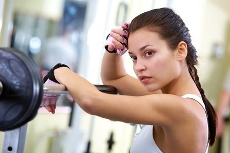 cuerpo femenino: Foto de ajuste morena con un dispositivo de levantamiento de pesas cerca Foto de archivo