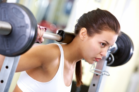 sweating: Photo of fit brunette practicing weightlifting Stock Photo
