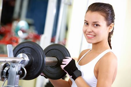 Photo of fit brunette looking at camera with weightlifting device near by photo