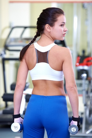 Rear view of young female with dumbbells during sport practice in gym photo