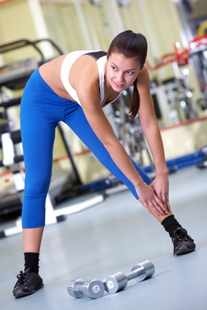 Photo of sporty brunette in sportswear standing on the floor and doing exercise in gym photo