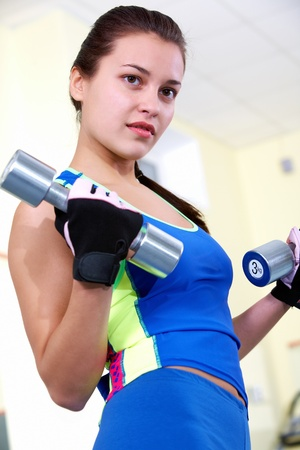 Portrait of young female with dumbbells doing exercises in gym Stock Photo - 11622347