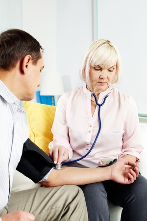 Portrait of mature woman measuring blood pressure of her husband at home Stock Photo - 11622366