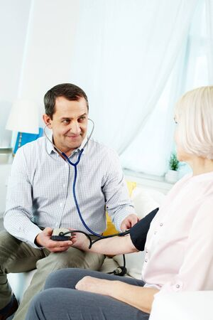 Portrait of mature man measuring blood pressure of his wife at home Stock Photo - 11622362