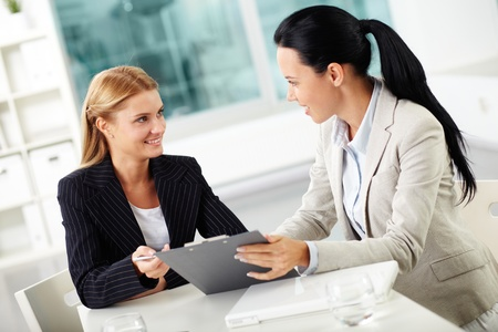 interacting: Portrait of two young women at workplace planning work together  Stock Photo