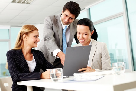 Three business people discussing papers with current results Stock Photo - 11634020