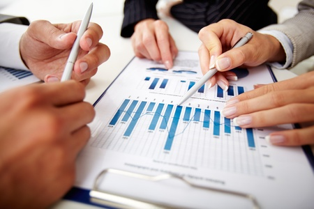 Image of human hands with pens over business document at meeting photo