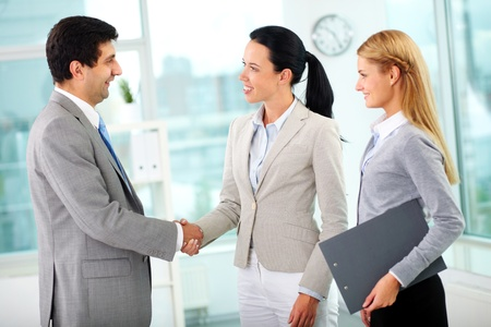 dedicated: Portrait of successful associates handshaking after striking deal