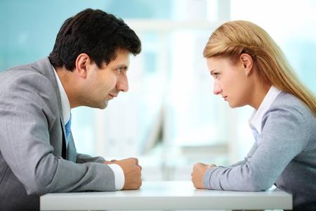 argument: Los perfiles de los empleados serios mirándose unos a otros
