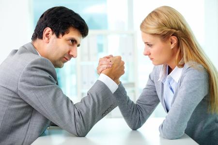 El hombre y la mujer en el gesto del brazo de lucha libre en la mesa de trabajo durante la reunión Foto de archivo