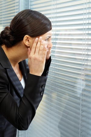 Image of puzzled businesswoman looking through jalousie in office photo