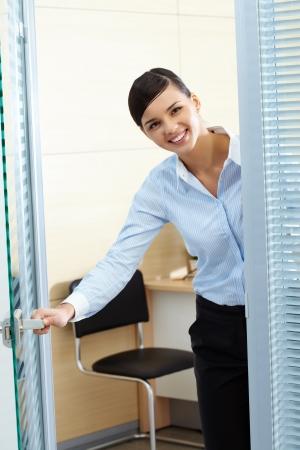 직업: 젊은 예쁜 비서가 사무실 문을 열고 카메라를 찾고 이미지 스톡 사진