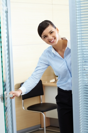 welcome door: Image of young pretty secretary opening office door and looking at camera