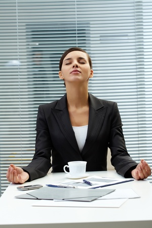 Image of young employer at the table and meditating photo