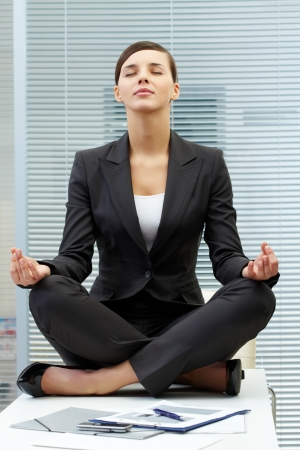 Image of young employer on workplace and meditating photo