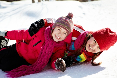 winterwear: Happy girls in winterwear looking at camera while playing outside Stock Photo