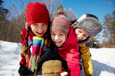 Happy friends in winterwear looking at camera while having fun outside photo
