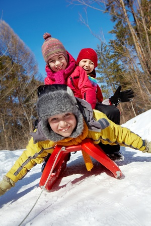 winterwear: Happy friends in winterwear looking at camera while tobogganing Stock Photo