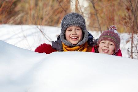 Happy friends in winterwear peeking out of snowdrift outside Stock Photo - 11640862
