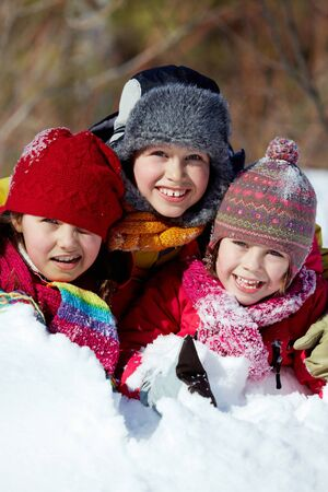 Happy friends in winterwear playing in snowdrift outside Stock Photo - 11640872