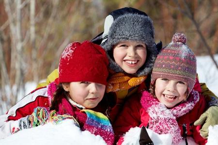 Happy friends in winterwear playing in snowdrift outside photo