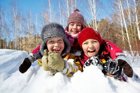 snow woman: Happy children in winterwear laughing while playing in snowdrift outside