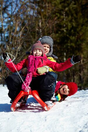 Happy friends in winterwear tobogganing in park Stock Photo - 11640898