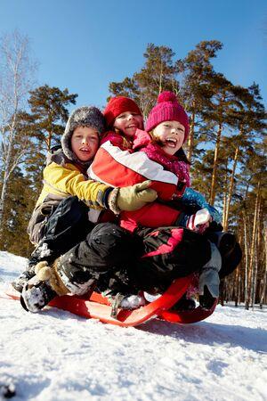 winterwear: Happy friends in winterwear tobogganing in park