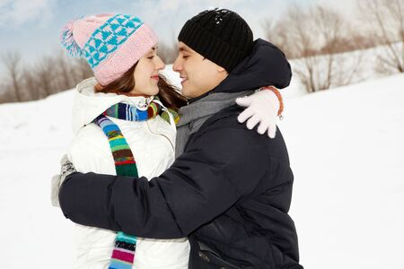 Portrait of happy couple in warm clothes embracing each other in winter  photo