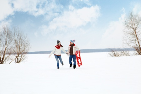 Portrait of happy couple in warm clothes running outdoors in winter  photo