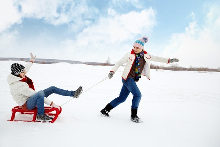 Portrait of happy couple in warm clothes tobogganing in winter  photo