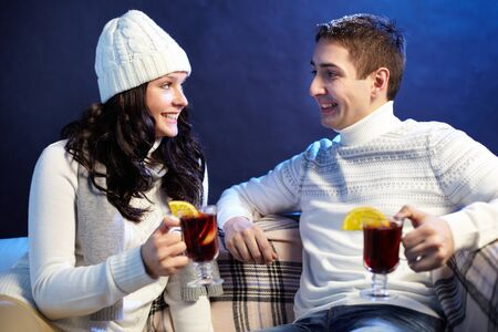 Portrait of happy couple holding glasses of hot tea with lemon while looking at one another