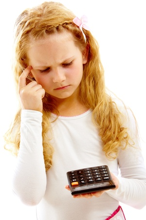 sumas: Retrato de ni�a linda mirando la calculadora al hacer las sumas Foto de archivo