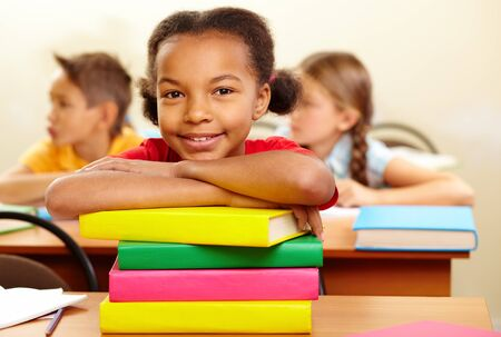 junior education: Portrait of lovely girl with stack of books looking at camera at workplace Stock Photo