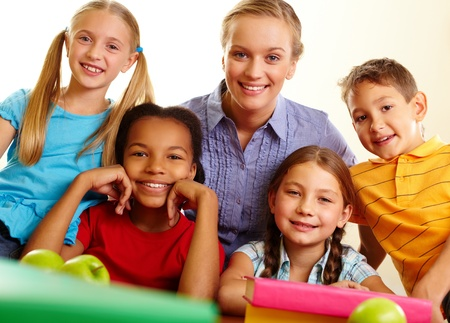 place to learn: Portrait of smart schoolchildren and their teacher looking at camera in classroom Stock Photo