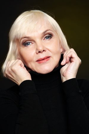 pensionary: Portrait of mature blond female looking at camera on black background Stock Photo