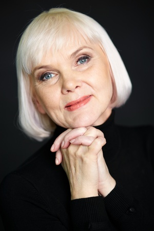congenial: Portrait of mature blond female looking at camera on black background Stock Photo