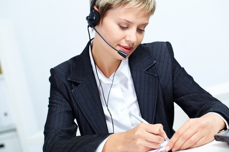 Portrait of young secretary with headset making notes Stock Photo - 11809490